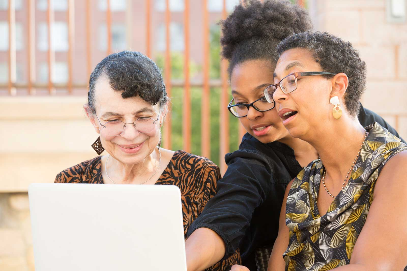 multigenerational family looking at something exciting on laptop