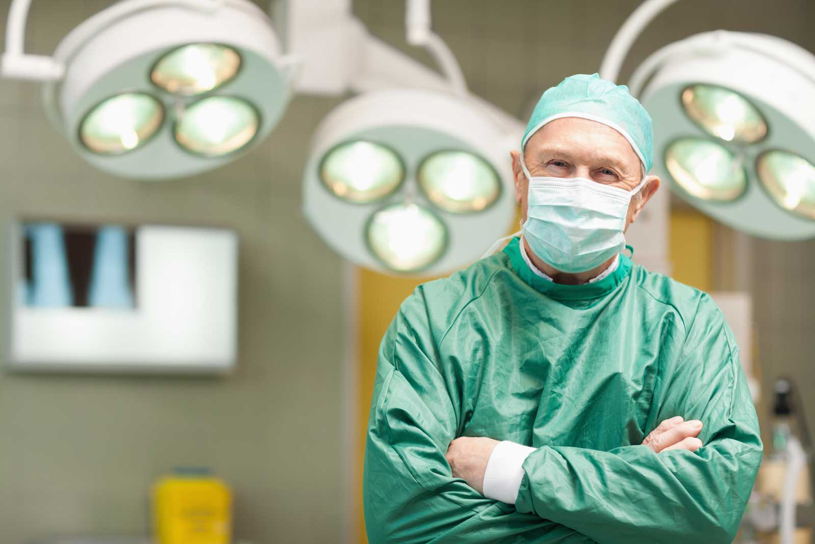 Smiling surgeon crossing his arms while standing