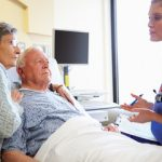 Male patient and spouse getting instructions before going home from hospital